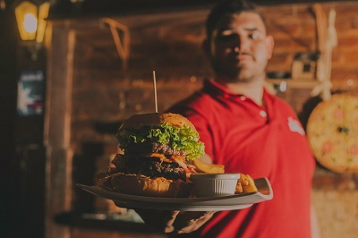 image of man serving burger in a restaurant