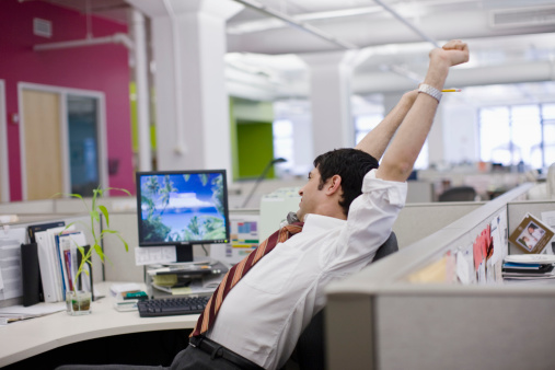 image of man stretching at desk