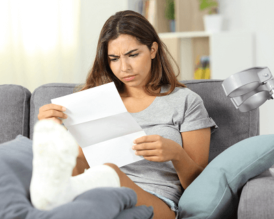 Woman with cast on her leg propped up on coffee table looks puzzled at a piece of paper