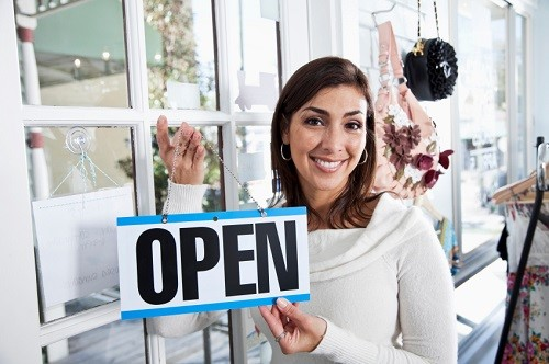 retail working holding up an open sign